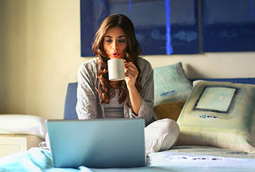 Decorative image of woman looking at laptop while drinking coffee on a bed