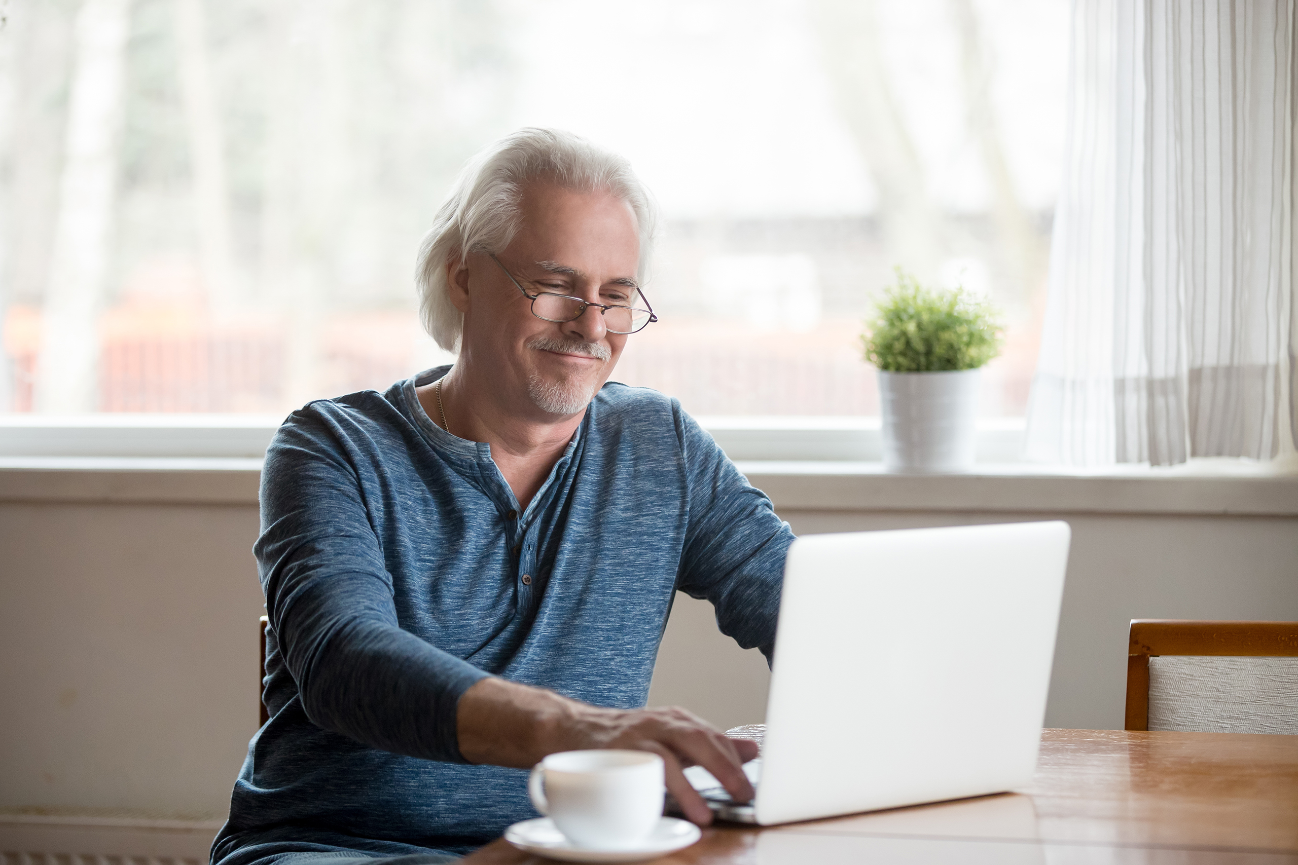 Smiling senior man in glasses working on laptop at home