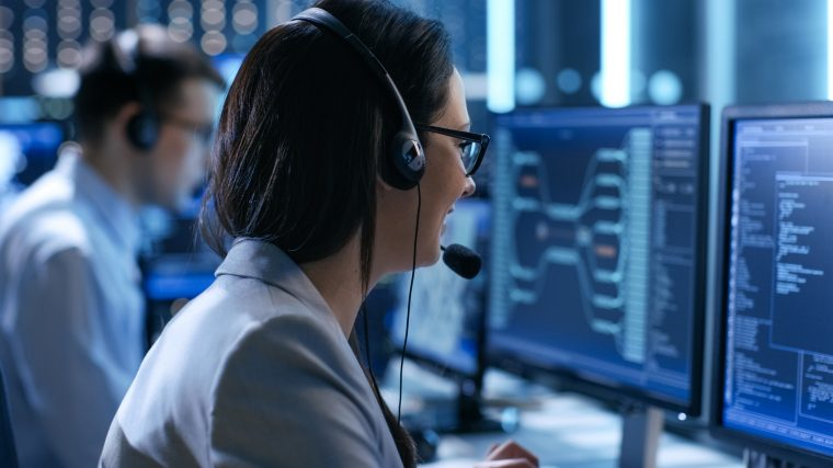Woman working on computer in a Technical Support wearing headset and looking at screen