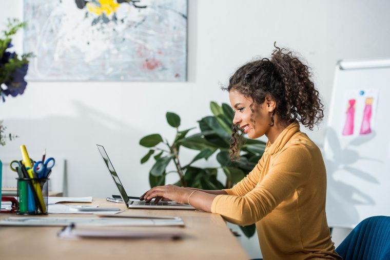 African american woman using laptop while sitting at desk in bright office