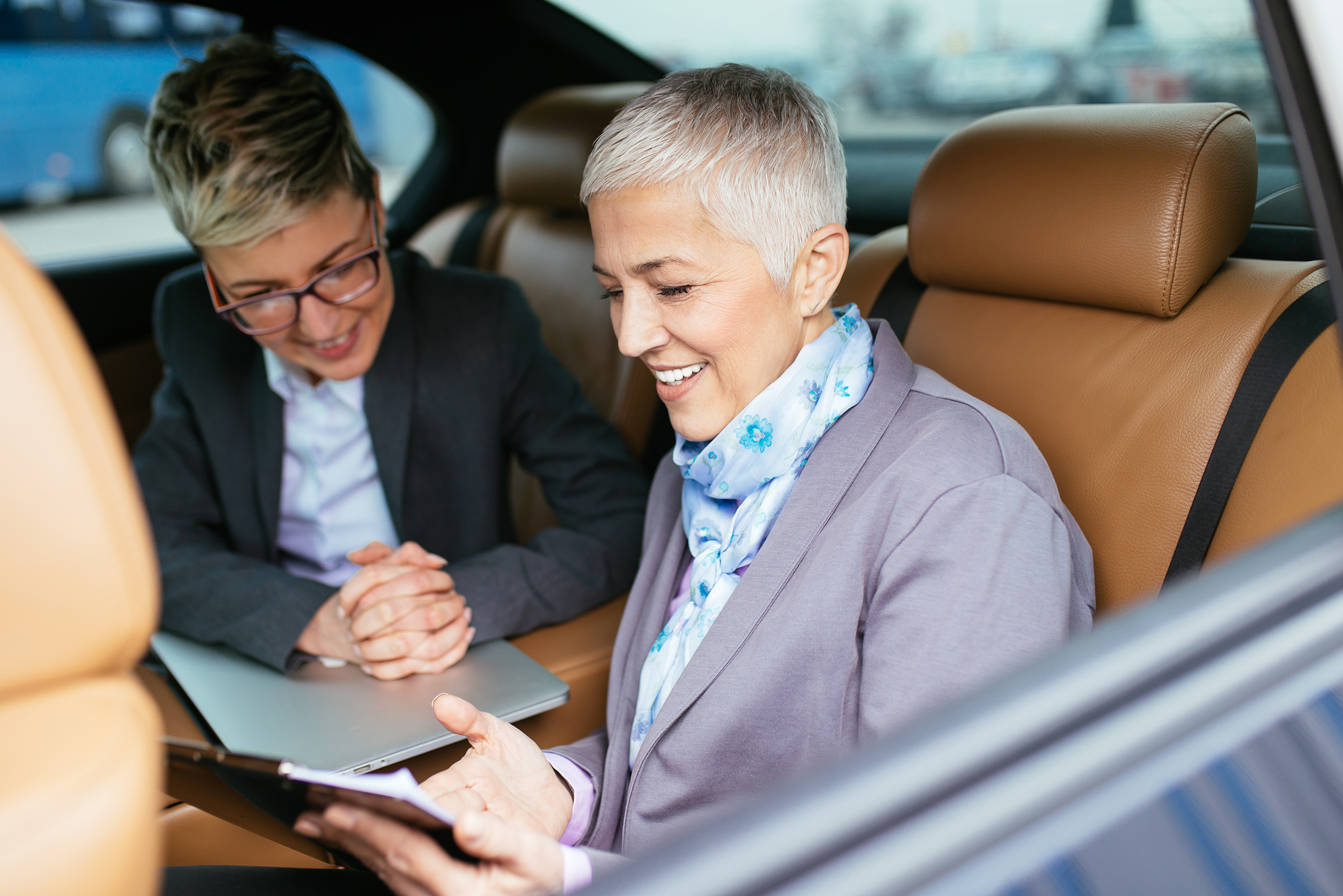 senior business woman with her assistant sitting in back of car texting message on mobile