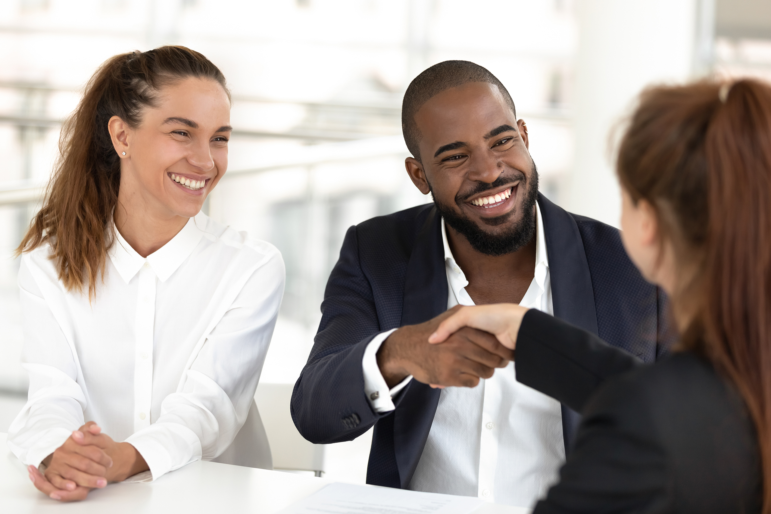 Happy mixed ethnicity couple clients handshake insurer realtor broker make agreement, african hr shake hand of caucasian candidate hiring at job interview, recruiting and insurance loan deal concept