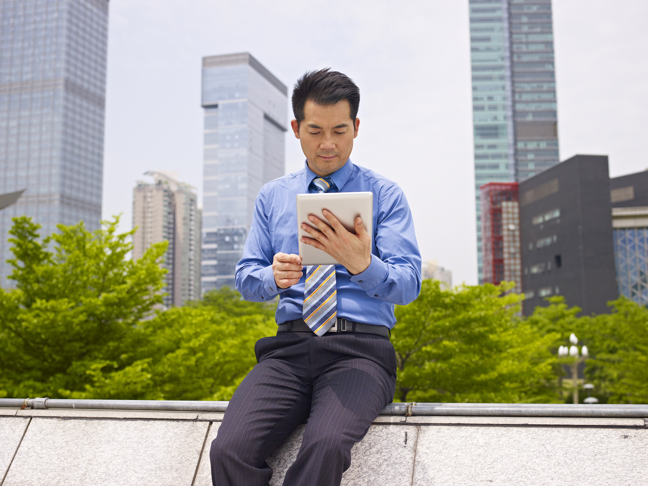 asian business executive looking at tablet computer.