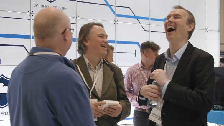 Echoworx team at trade show laughing with clients
