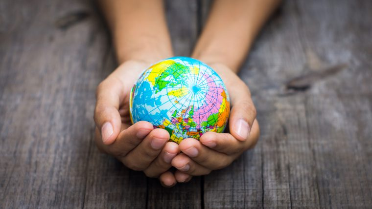 A person holding a globe on wooden background.