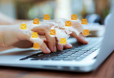 Closeup of hand typing on a laptop keyboard with 3D graphic email icons floating in air