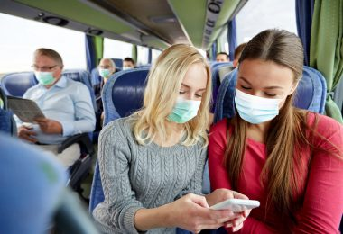 Two woman wearing face masks sitting on a bus reading something on mobile device