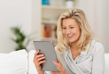 White mature woman looking at her tablet while sitting on a couch
