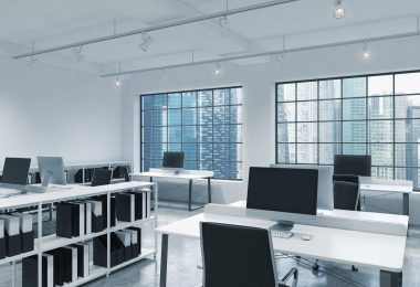 Modern office with open concept large monitors on long white tables