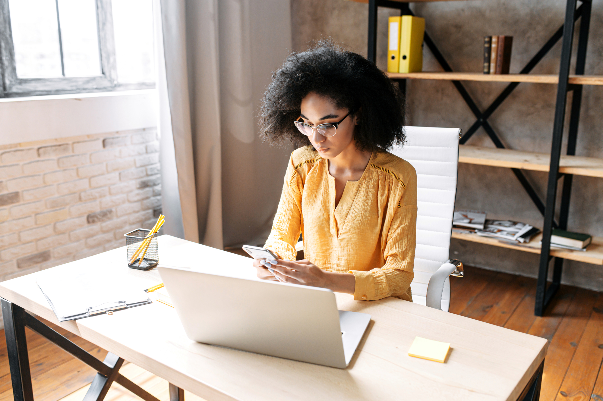 Attractive african american business woman is using mobile phone while sitting at the desk with laptop in a modern office